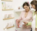 Two pregnant women shopping, choosing greeting cards
