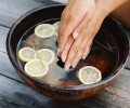Woman dipping her hands in a bowl with lemon slices