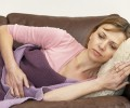 Stock Photos: WOMAN UNWELL AND LYING ON SOFA