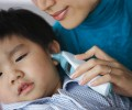 Mother Taking Son's Temperature --- Image by © Redlink Production/Corbis